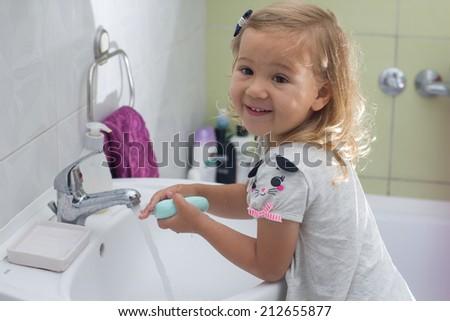 Little girl washing her hands in bathroom. - stock photo