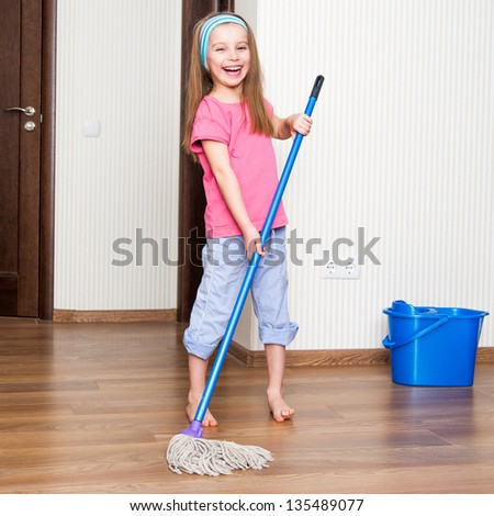 little girl washing the floor with a mop at home - stock photo
