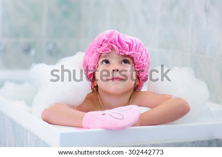 Little girl washing with a bubbles in bath in a hat - stock photo