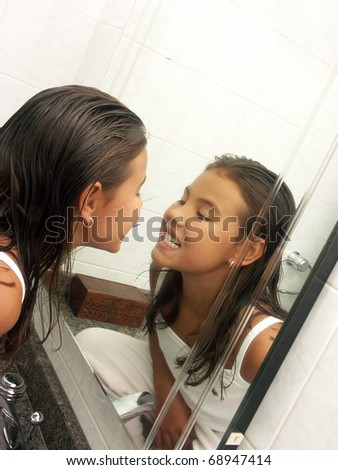 Little girl watching herself at mirror. Little girl watching her teeth. - stock photo