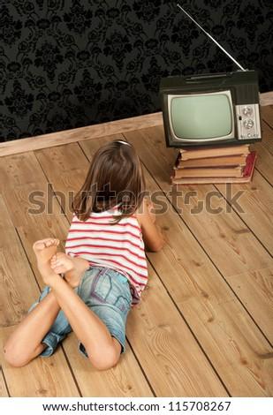 little girl watching old retro tv - stock photo