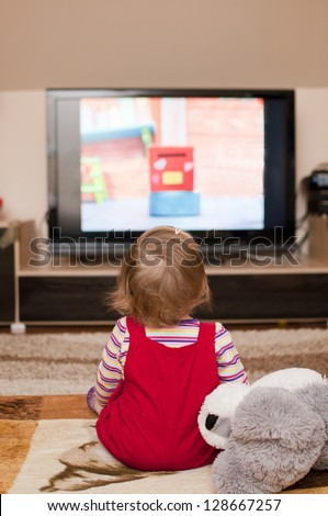 little girl watching television - stock photo
