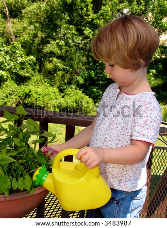 Little girl watering flowers - stock photo