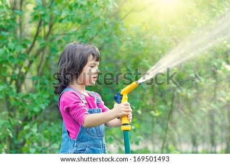 Little girl watering garden - stock photo