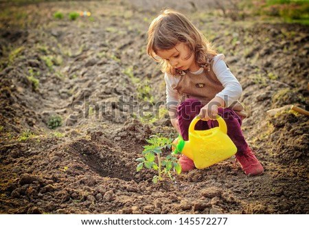 Little girl watering plants in a garden - stock photo