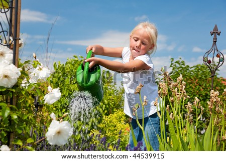 Little girl watering the flowers in the family garden at a summer day, very rural scene - stock photo