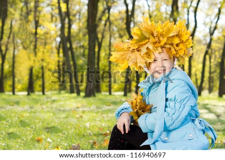 Little girl wearing a crown of colourful yellow autumn leaves on her head as she sits smiling happily in fall woodland - stock photo