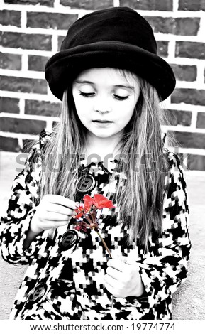 Little girl wearing a hat and coat holding a flower - stock photo