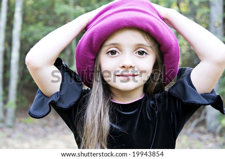 Little girl wearing a hat with hands on her head - stock photo