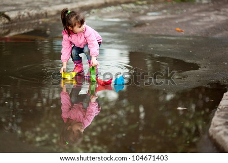 little girl, wearing a pink jacket, playing with colorful paper ship, in the puddle - stock photo