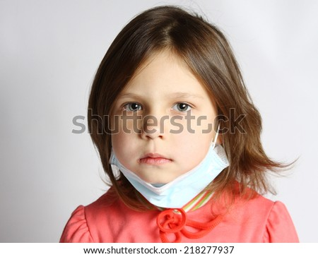 Little girl wearing a protective mask with thermometer - stock photo