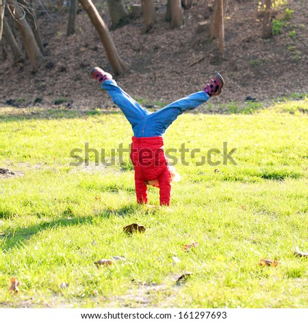 Little girl wearing a red standing on hands upside down on green grass in an urban neighborhood.  - stock photo