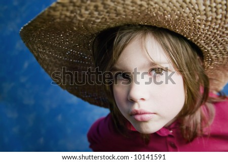 Little girl wearing a straw cowboy hat with a neutral expression - stock photo