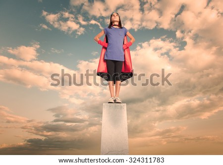 little girl wearing a superhero costume on a pedestal - stock photo