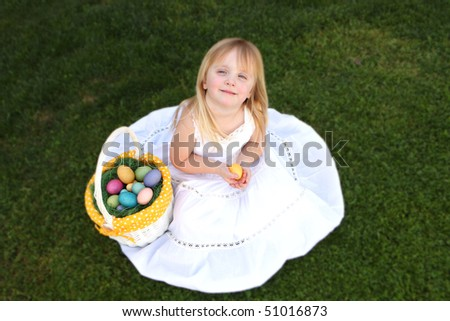 Little Girl Wearing a White Dress Holding Easter Eggs on Green Grass Outdoors - stock photo