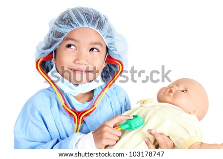 Little girl wearing doctor's operating gown examining a doll patient with toy stethoscope. - stock photo