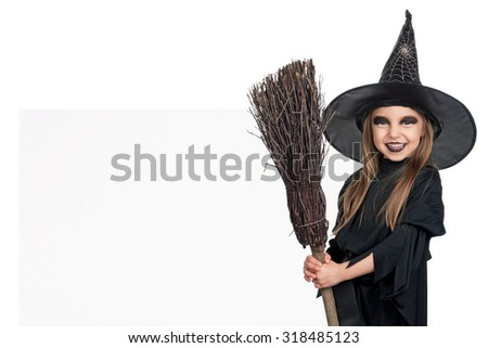 Little girl wearing halloween costume with broom and blank board on white background - stock photo