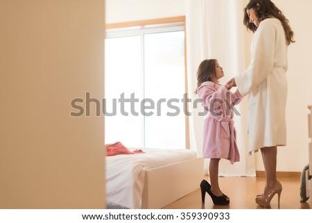 Little girl wearing heels with her mother in bedroom - stock photo