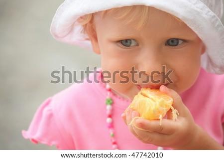 little girl wearing panama hat is eating orange. focus on orange in hand. - stock photo