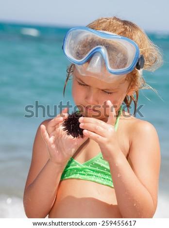 Little girl wearing snorkeling mask looking at sea urchin - stock photo