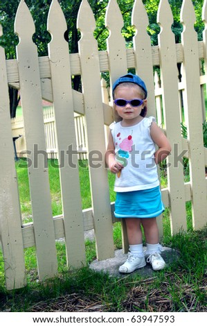 Little girl wearing sunglasses and a cap turned backwards, stands besides a wooden picket fence. - stock photo