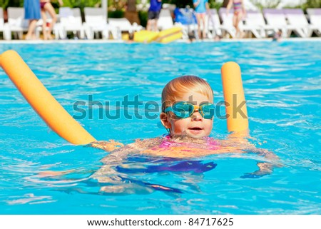 Little girl wearing swimming goggles learning to swim with pool noodle - stock photo