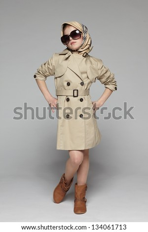Little girl wearing trench coat and sunglasses, with scarf over her head, over gray background - stock photo