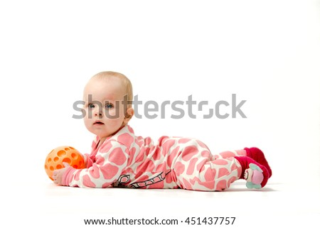 Little girl wearing white and pink pyjama, red socks is playing with her orange ball while lying on a belly - stock photo