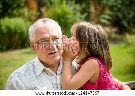 Little girl whispering her grandfather a secret to ear - outdoor in backyard - stock photo