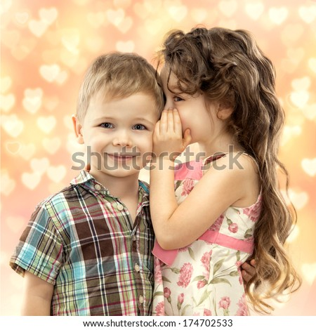 Little girl whispering something to boy. Love concept - stock photo