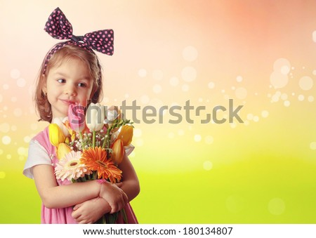 Little girl wih wreath with bow on head holding spring flowers bouquet.  - stock photo
