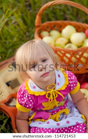 Little girl with a basket of fresh apples - stock photo