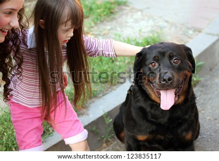 Little girl with a big black dog - stock photo