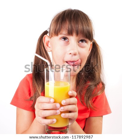 Little girl with a big glass of orange juice - stock photo