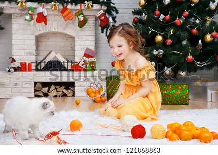 Little girl with a cat in a holiday room - stock photo