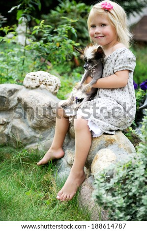 Little girl with a cute puppy dog sitting outdoors - stock photo