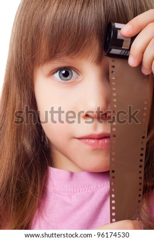 Little girl with a film from the camera - stock photo