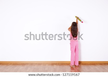 Little girl with a giant pencil writing on the wall - stock photo