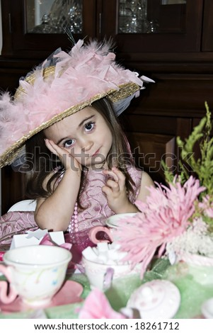 Little girl with a great expression on her face wearing a tea party hat and pink pearls. - stock photo