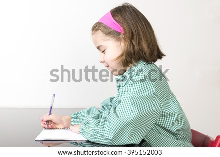Little girl with a green plaid smock writing in a notebook at home - stock photo