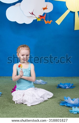 Little girl with a lollipop on the flower meadow - stock photo