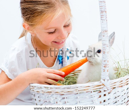 Little girl with a rabbit and carrot in a basket - stock photo