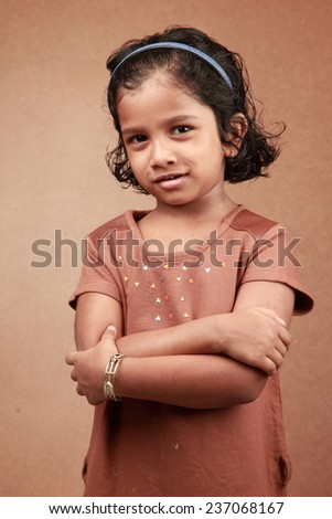 Little girl with a smiling face against a wooden background - stock photo