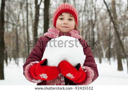 Little girl with a snowball in his hands against the tree - stock photo