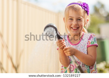 Little girl with a water sprinkler - stock photo