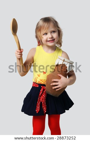 Little girl with a wooden spoon and crock on a grey background - stock photo