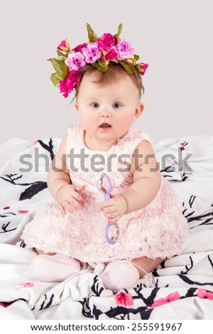 Little girl with a wreath of flowers on her head with a rattle in hands sitting on a blanket - stock photo
