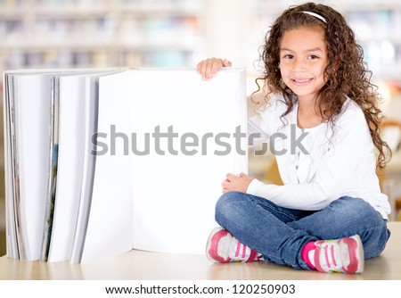 Little girl with an open book at the library - stock photo