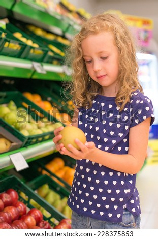 Little girl with apple in grocery store. - stock photo