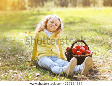 Little girl with autumn basket and apples outdoors - stock photo